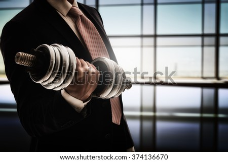 successful business man holding a heavy dumbbell. the concept of success in a hard work of business. - stock photo