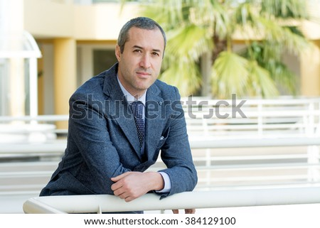 Successful business man looking confident and smiling, outside office