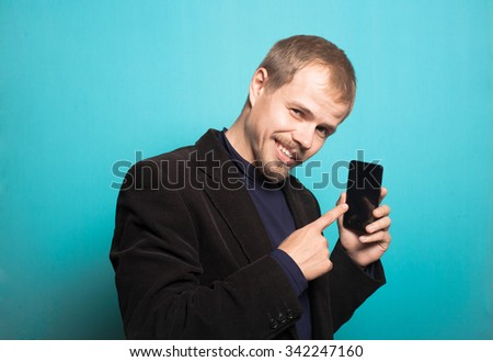 successful business man points a finger on the phone, with a beard and mustache, office style studio photo isolated on a blue background