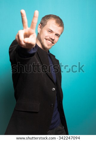 successful business man showing a sign of PEACE, with a beard and mustache, office style studio photo isolated on a blue background - stock photo