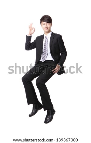 Successful business man sitting on something and show ok hand sign isolated against white background, asian male model - stock photo