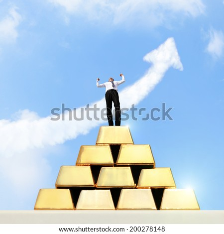 Successful business man standing on gold bullion with sky and growth arrow cloud - stock photo