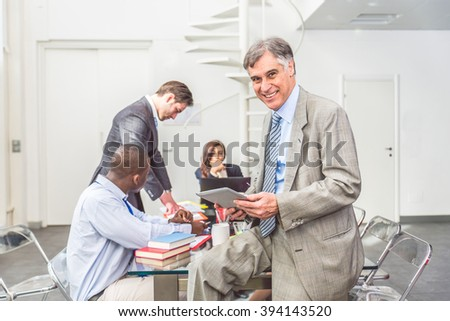 Successful business man standing with his staff in background at office - Senior manager looking confident at camera - stock photo