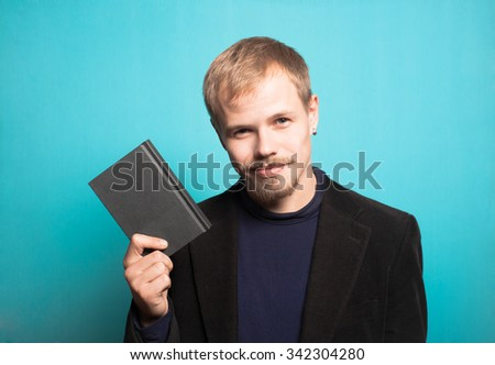 successful business man with a notebook in his hand, with a beard and mustache, office style studio photo isolated on a blue background - stock photo