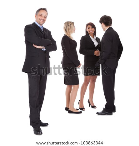 Successful business man with colleagues at the back rejoicing success - stock photo