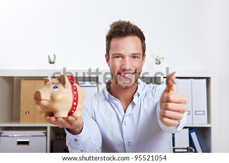Successful business man with piggy bank holding thumbs up in office - stock photo