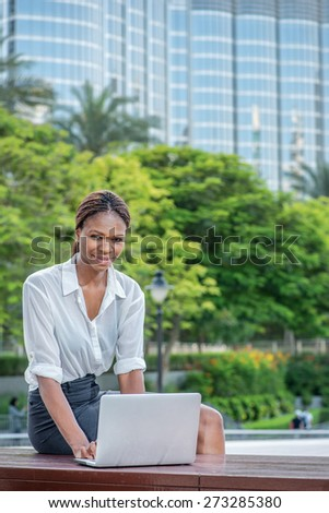Successful business over laptop in Dubai. Smiling African businesswoman businessman sitting in the street and working at laptop in Dubai downtown among green trees while looking directly at the camera - stock photo