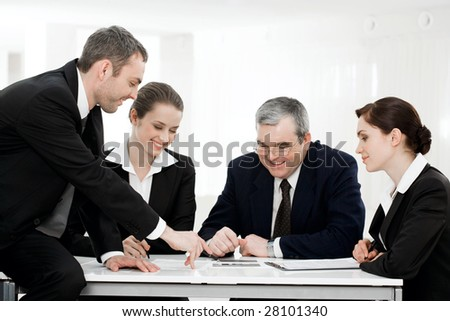 Successful business partners looking at new plan with smiles at working meeting