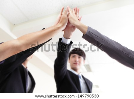 Successful business people group celebrating with hands giving high five at office,focus on hans, asian people - stock photo