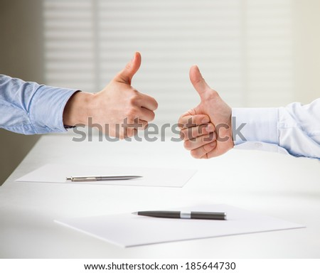 Successful business people showing thumbs up sign after making agreement - stock photo