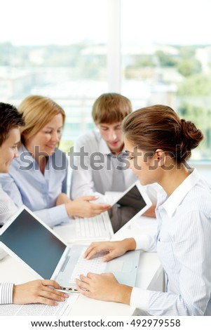 Successful business people sitting at the table and using laptop