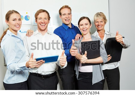 Successful business people team in office holding many thumbs up - stock photo