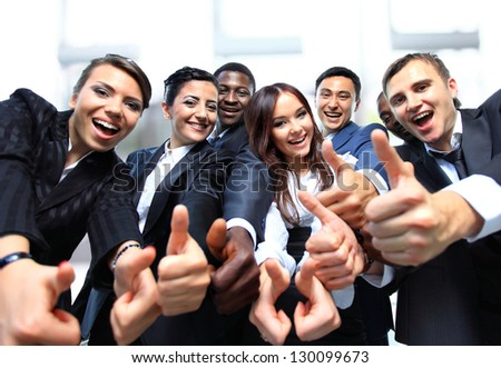 Successful business people with thumbs up and smiling