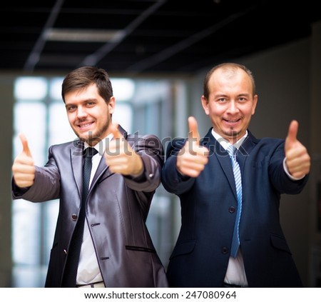 Successful business people with thumbs up and smiling - stock photo