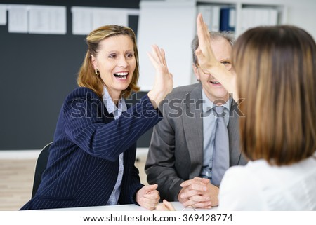 Successful business team congratulating each other as two woman give a high fives hand gesture while cheering