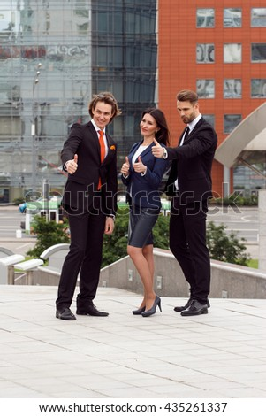 Successful business team. Full length of group of confident business people showing thumbs up standing close to each other and smiling.