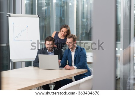 Successful business team is discussing the project on conference. The men are sitting at the table and smiling. The woman is standing and looking at the laptop with interest - stock photo