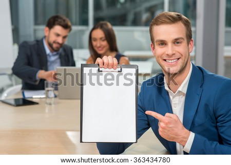Successful business team is taking part in a conference. They are sitting at the table and using notebook. The man is holding a folder of documents and pointing finger at it. They are smiling - stock photo