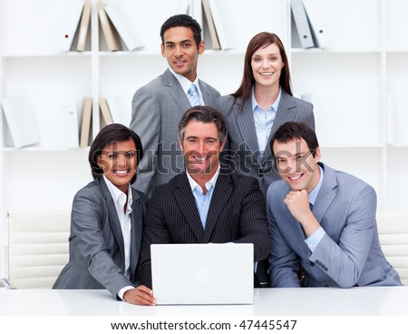 Successful business team looking at a laptop in the office - stock photo