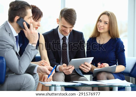 Successful business team of four sitting in office and planning work