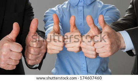 Successful business team showing thumbs up - closeup shot