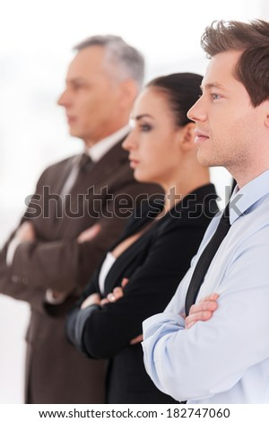 Successful business team. Side view of confident people in formalwear keeping arms crossed while standing in a row and looking away