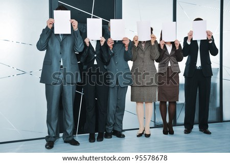 Successful business team standing holding white papers - stock photo