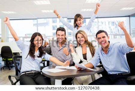 Successful business team with arms up at the office - stock photo