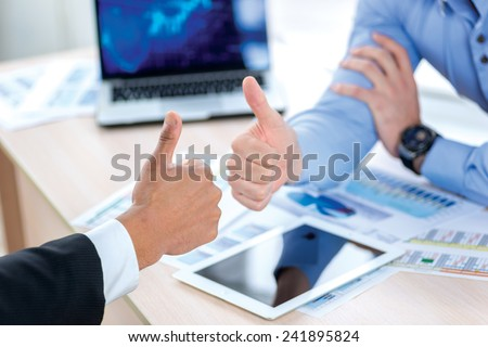 Successful business. Two Confident businessman sitting at the negotiating table in the office and show a thumbs up Close-up view of hands. Business people dressed in formal wear - stock photo