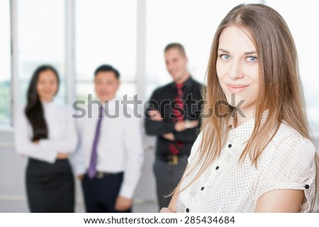 Successful business woman at foreground and business team of men and woman at background. Image symbolizes a successful corporation or company where achieve success for intelligent and beautiful women