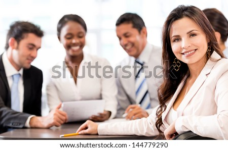Successful business woman at the office with her team - stock photo