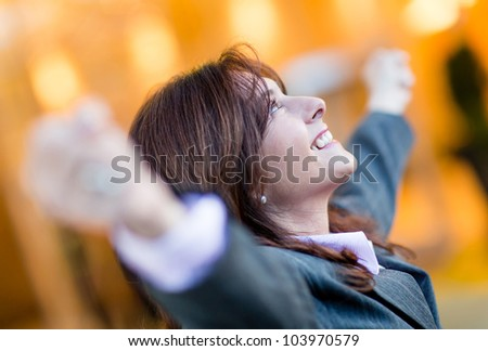 Successful business woman celebrating with arms open