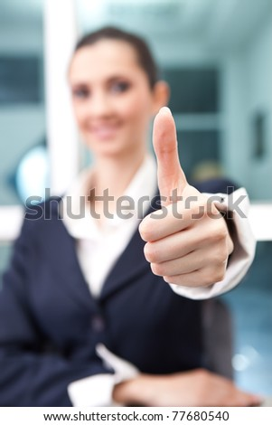 successful business woman giving a thumbs up (thumb in focus)