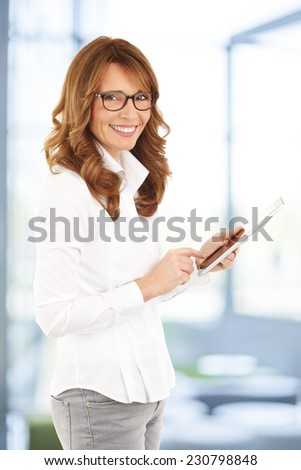 Successful business woman holding tablet in her hands while standing at office.  - stock photo