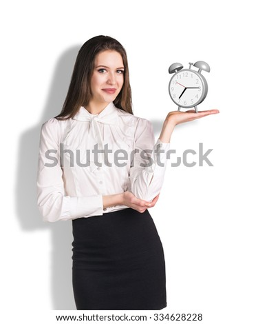 Successful business woman holding the alarm clock isolated on white - stock photo