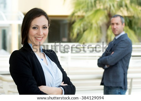 Successful business woman looking confident and smiling, outside office