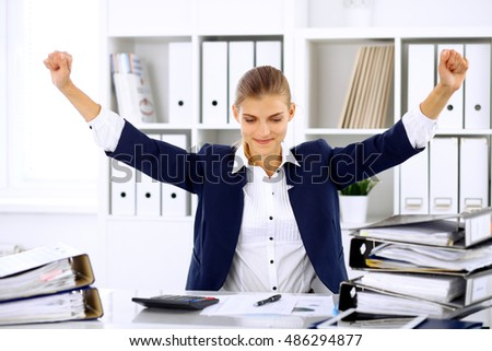 Successful business woman or female accountant with hands up
