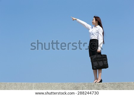 Successful business woman pointing something with blue sky, asian beauty