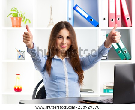 Successful business woman showing thumbs up at her workplace. Happy female broker sitting at computer desk in the office.  - stock photo