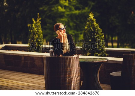 successful business woman sitting in a cafe and smiling talking on the phone - stock photo