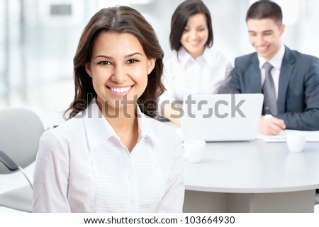 Successful business woman sitting with her team at office