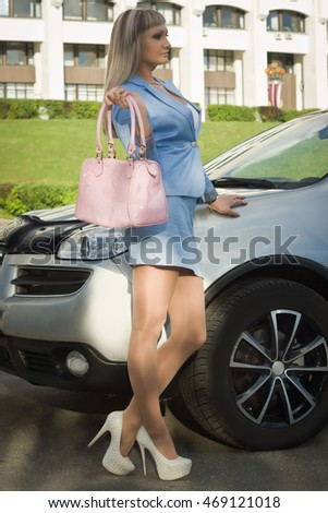 Successful business woman standing in the street background car
