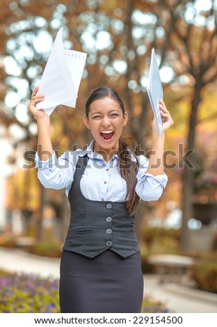 Successful business woman with arms up celebrating. Portrait winning young ecstatic student being winner isolated outside fall background. Positive emotion face expression. Life achievement concept - stock photo