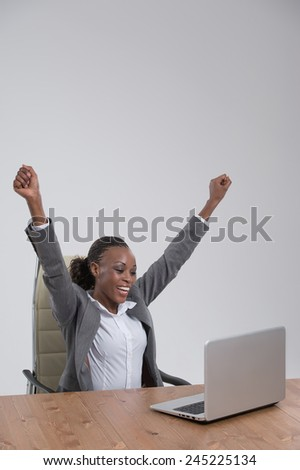 Successful business woman with arms up sitting in front of laptop at office - stock photo