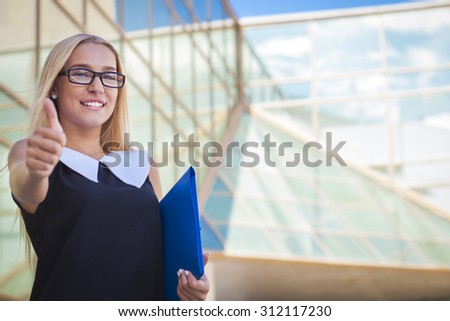 Successful business woman with thumb up modern building - stock photo