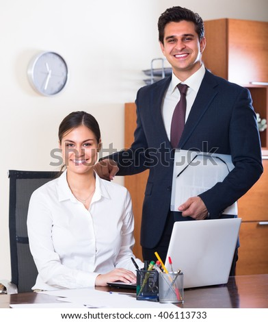 Successful businessman and his smiling young  assistant at the desk in modern office
