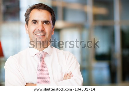 Successful businessman at the office looking confident - stock photo