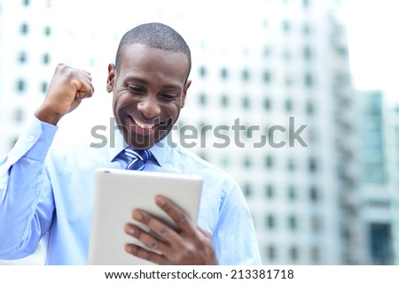 Successful businessman clenching fists with digital tablet - stock photo