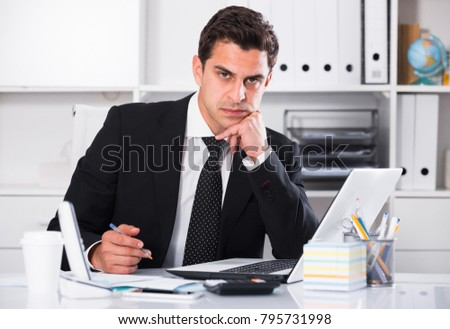 Successful businessman concentrating on work on laptop in office