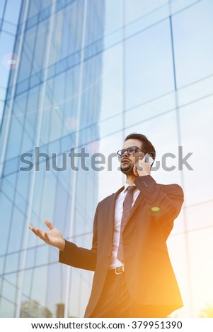 Successful businessman dressed in elegant suit talking on cell telephone during work break outdoors, professional male manager having serious mobile phone conversation while standing near skyscraper - stock photo